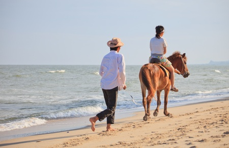 cha: teen practice to ride a horse on sea beach Stock Photo