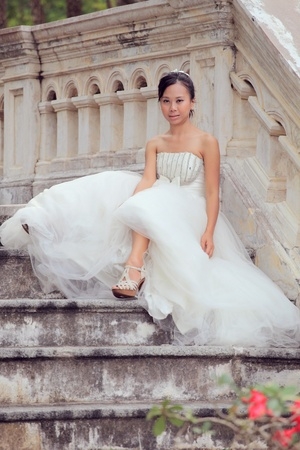 women in white bride sitting on stairway photo
