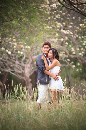 couple of asian people hug in the park with flowers blooming photo