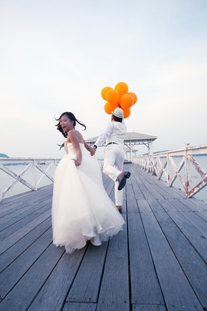 honeymoon couple: couple of man and women in wedding suit glad emotion on wood bridge