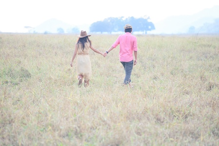 man and women wearing a hat walking in the grass field photo