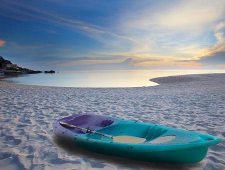 green sea kayak on sand beach photo
