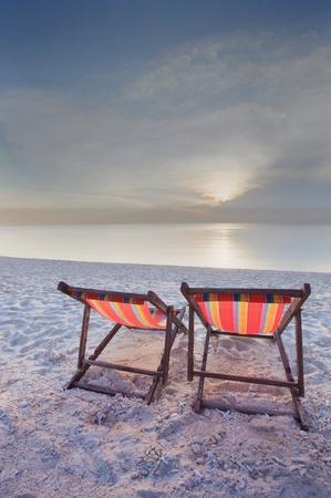 couples of wood teak chairs beacn and sun set scene photo