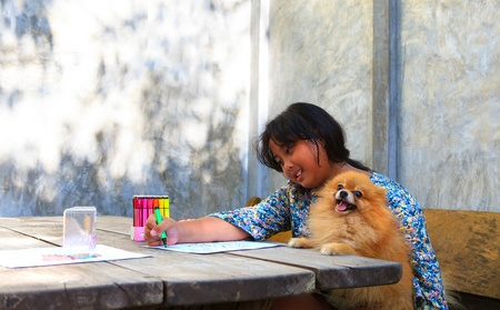 girl sitting and painting in home with pomeranian dog photo