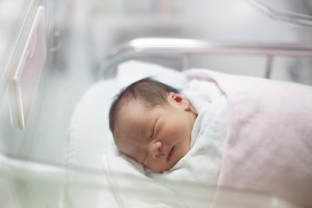 nacimiento bebe: bebé recién nacido duerme en la manta en la sala de partos Foto de archivo
