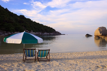 couples chairs beach and umbrella at sea side photo