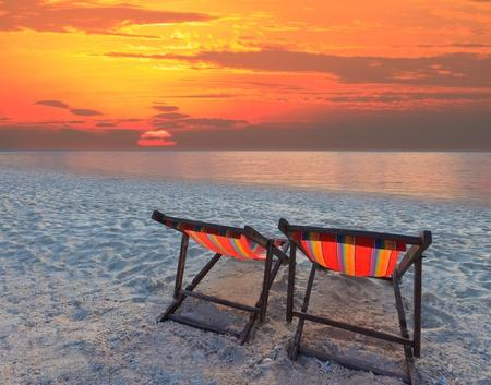 silla de madera: sillas de parejas playa en la playa de arena con el cielo de colores