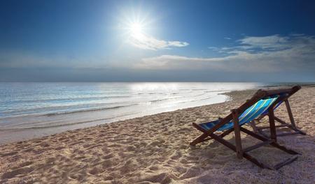 sedie a sdraio sulla spiaggia di sabbia e sole splendente nel cielo Archivio Fotografico