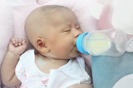 face of infant  drinking mother milk from bottle Stock Photo - 13646241