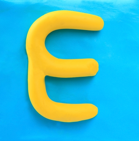 yellow clay alphabet letter with drop shadow on blue clay photo