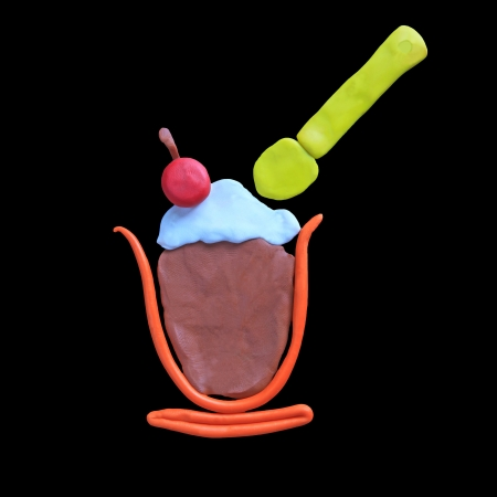 ice cream with cherry topping and spoon isolated black photo