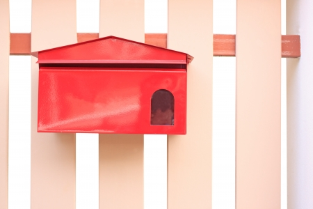 red mail box hanging on fence photo
