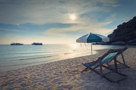 madeira cadeiras cama e guarda-sol na areia da praia no sol tempo definido Imagens