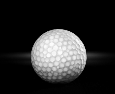 playing golf: old used golf ball on black background