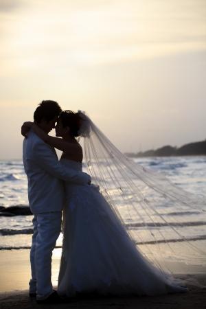 noiva e noivo segurando e abraço a beira-mar em tempo escuro Imagens