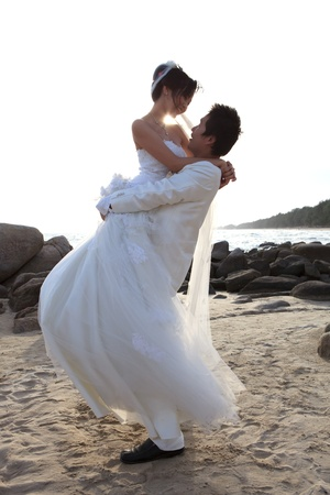 man and woman  in wedding suit hug at sea beach