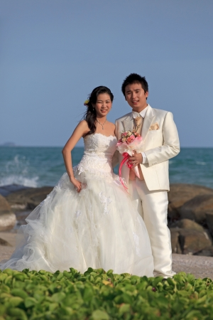 man and woman  in wedding suit at sea beach photo