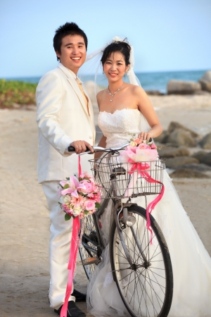groom and bride standing beside old bicycle photo