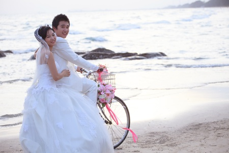 face of asian groom and bride riding bicycle on beach Stock Photo
