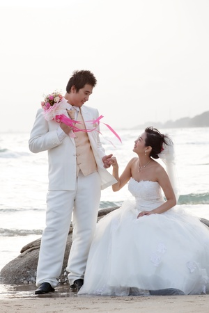 groom and bride on sea beach photo