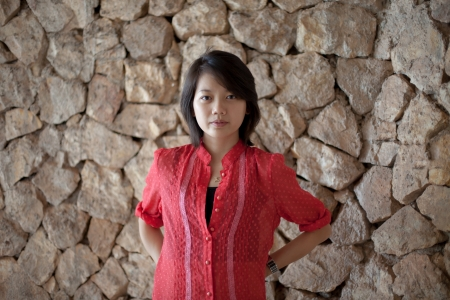 asian woman standing in font of rock wall photo
