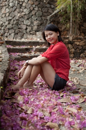 thai teen: asian woman sitting on ground with paper flowers fall