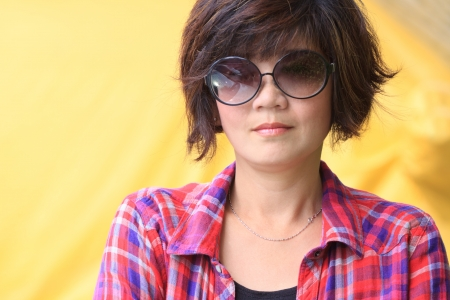 asian woman with eyes glasses  and red plaid shirts yellow background photo