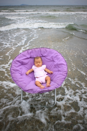 round chairs: baby sitting on round chairs at sea beach