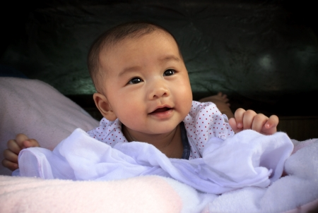 lied: asian baby smiling face lied on bed  Stock Photo