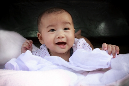 asian baby girl: asian baby smiling face lied on bed  Stock Photo