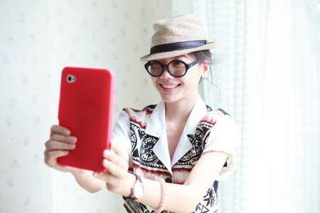 korean fashion: woman take a photo by smart phone tablet