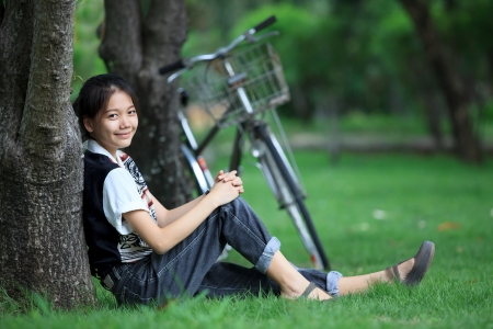 ecotourism: woman sitting in the green garden with bicycle background