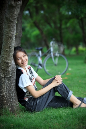 woman sitting in the green garden with bicycle background photo