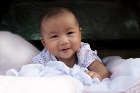 asian baby smiling face lied on bed  Stock Photo