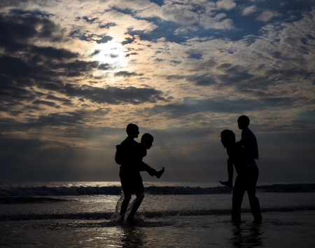 children playing on sea beach in the evening lignt photo