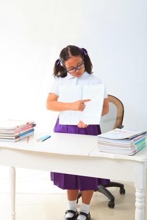 salle classe: fille debout et point un livre dans la salle de classe pour exp Banque d'images