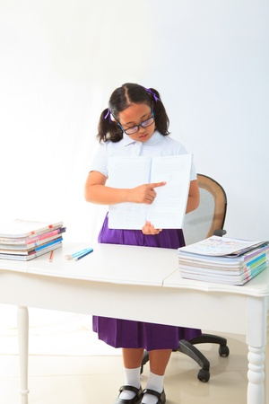 girl standing and point a book in class room for exp photo