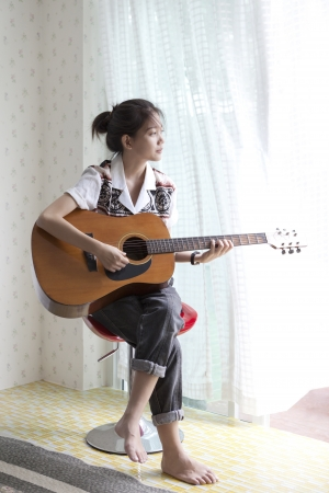 playing music: face of asian woman playing guitar Stock Photo