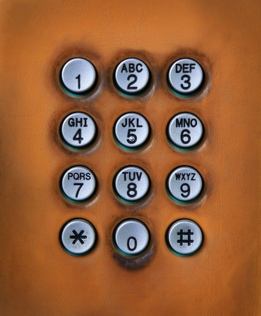 dialing pad: dial number button on old used public telephone