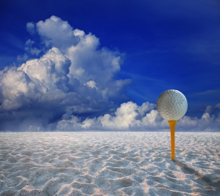 golf ball on yellow tee and and land scape of sand desert photo