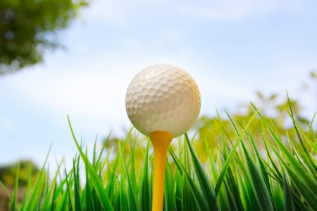 eye ball: golf ball on yellow tee and blue sky background Stock Photo