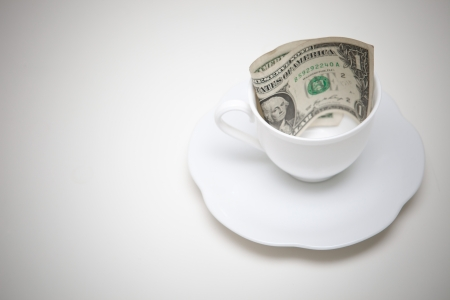 one dollars money in coffee cup