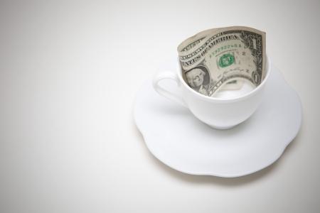 uma dólares do dinheiro no copo de café Imagens