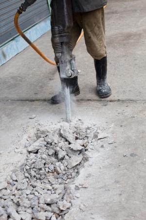 セメント地盤を掘削道路工事の労働者 写真素材