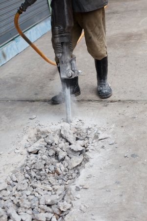 drilling: worker of road construction drilling cement ground
