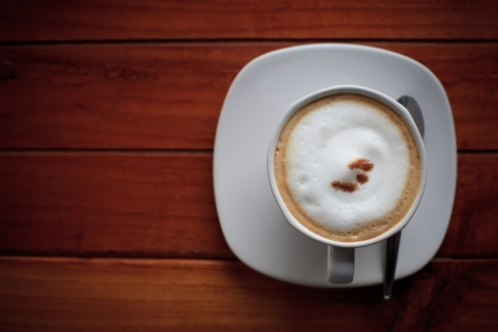 dress up of cappuccino coffee in white cup on brown wood background Stock Photo - 15550669