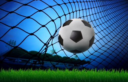 soccer football in goal net and stadium blue sky background