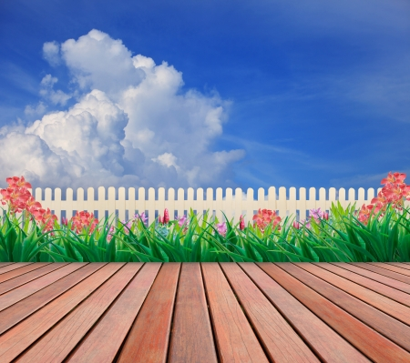 paper cut out: wood terrace and flower garden with blue sky background
