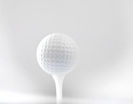 golf ball on tee and grey space background photo