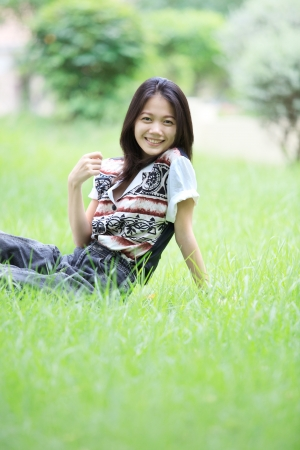 face of asian woman relaxing emotion sitting on grass field Stock Photo - 16491147